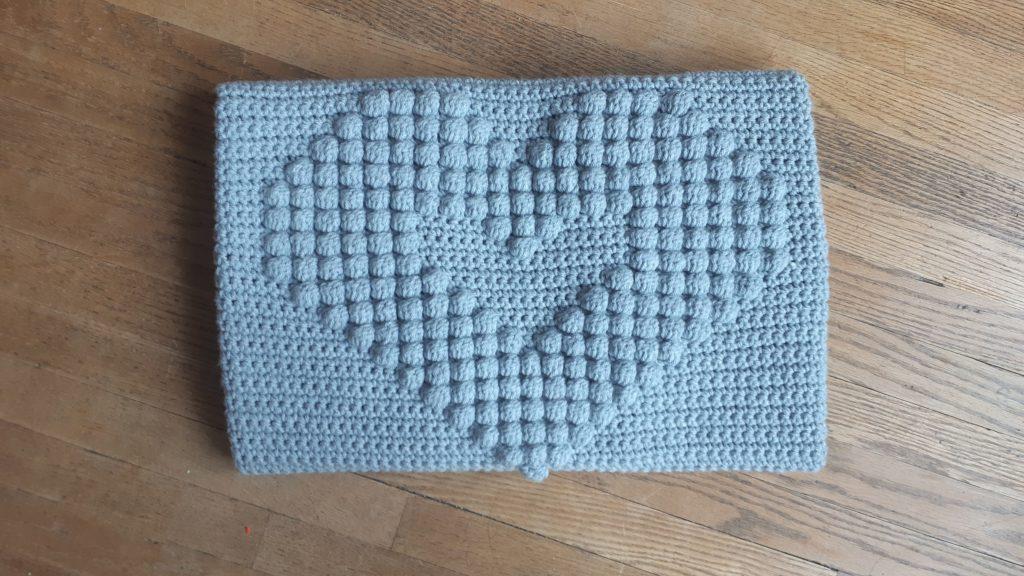 gran motivo de corazón de bobble en esta manta de crochet para bebé